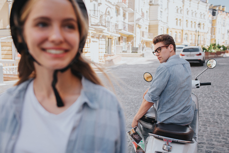 Nice and attractive girl is standing in front of camera in helmet and looking to the right. Guy is sitting on motorcycle behind her and looking at her. Girl is smiling.