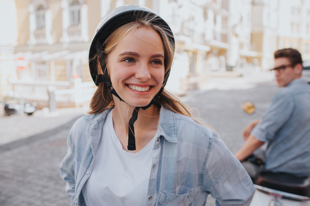 Another picture of happy girl standing in front of guy that is sitting on motorcycle behind her and looking back at her. Girl wears helmet.