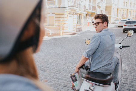 Attractive guy is sitting on motorcycle and looking back at girl. He is handsome and confident. Girl is looking at him. She wears helmet.