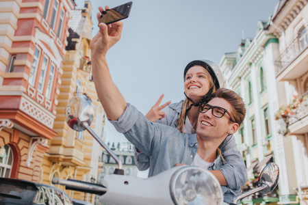 Guy is sitting on motorcycle with his girlfriend and taking selfie. He is holding phone in hand. They are smiling and posing on camera.