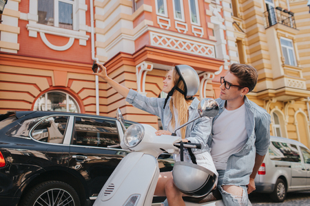 Blonde girl is sitting on bike with her boyfriend and takig selfie. She is holding phone in hand. They are posing on camera Stock Photo
