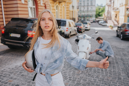 A picture of girl trying to catch car to help them fix motorcycle. It is need some repair. Girl is looking to the right and showing her thumb up. She is worried. Guy is fixing vehicle on the back. Stock Photo