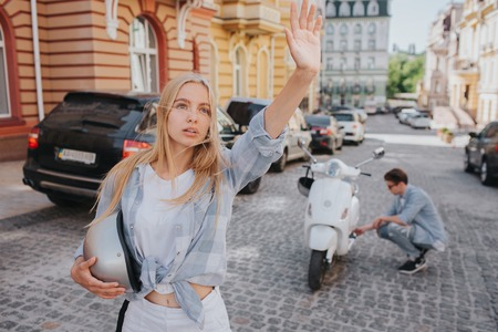 Girl is standing on road and waving with her hand. She is looking to the right. Her boyfriend is trying to fix problem with motorcycle. They are standing in middle of road.