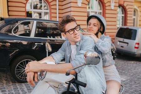 Tired girl is sitting behind her boyfriend on motorcycle and leaning to him. She is looking at him. Guy is leaning to control handles and looking to the right. He looks confident. Stock Photo