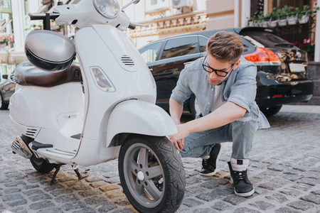 A picture of guy sitting in squat position and looking at motorcycles wheel. He is trying to fix it. Guy looks worried and serious. Stock Photo