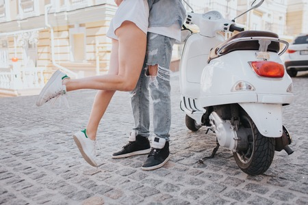Girl is jumping near guy. Her legs are in air. They are standing beside motorcycle in the middle of street. They have a date today.