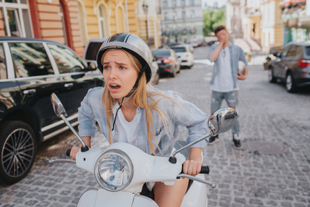 Worried girl is sitting in motorcycle and looking forward. She is upset. She cant start to ride. Guy is standing on the back and covering his face with hand. He is frustrated.