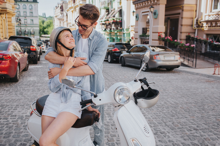 Lovely couple are sitting together on motorycle. Guy is embracing his girlfriend. She is smiling and looking at him. She wears helmet. They look happy. Stock Photo