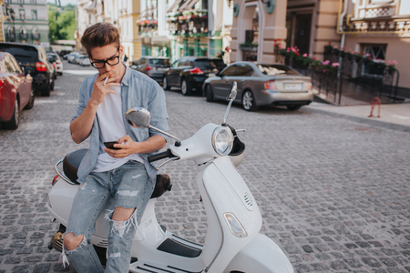 Handsome guy is sitting on motorcycle and holding phone in hand Stock Photo