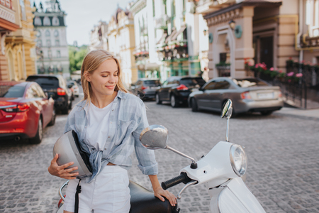 Lovely girl is sitting on motorcycle and looking at it. She is holding helmet in hand and smiling. Girl is happy. Foto de archivo