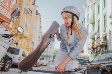 Smart and good-looking girl is looking under motorcycle seat. She is looking for something. Girl is standing outside on street.