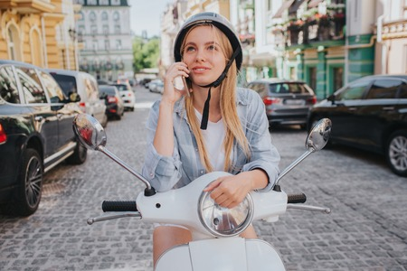 Gorgeous blonde girl in helmet is posing on camera. She is smiling. Girl is sitting on motorcycle in the middle of street. She looks happy.