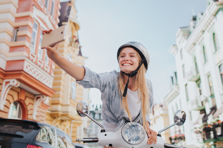 Girl is sitting and leaning to motorcycles and taking selfie. She is holding phone in hand. Girl is looking on camera and smiling.