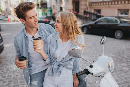 Beautiful couple is sitting together on motorcycle and looking at each other. They are holding cups of coffee in hands. They are having some rest and fun. Stock Photo