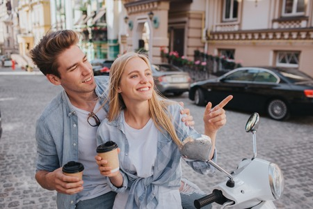 Beautiful couple is sitting together on motorcycle anf looking at each other. They are holding cups of coffee in hands. They are having some rest and fun.