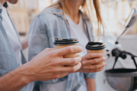 Close up of guys and girls hands holding cups of coffee. This people are sitting on motorcycle and having some rest.