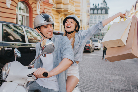 Happy girl is holding shopping bags in hand and enjoying. She is looking up and smiling. Guy is driving motorcycle. He is looking at her and smiling.