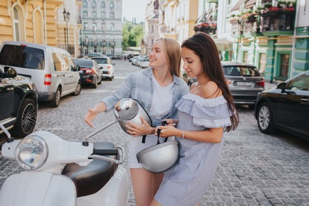 Two girls are riding on one motorcycle. Chinese girl is in a front. Brunette girl is sitting in the middle. The last one is blonde girl. They are smiling and enjoying the ride. Stock Photo