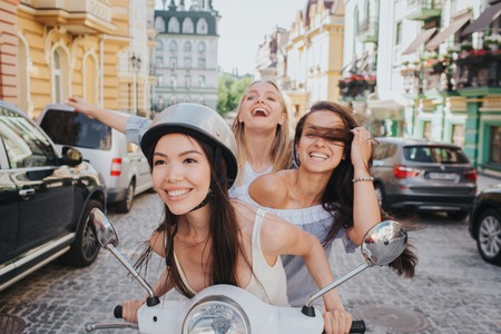 Excited and gorgeous friends are riding on one motorcycle. Chinese girl is smiling. She is wearing helmet. Her friends are laughing out loud and looking up and straight. They are very happy.