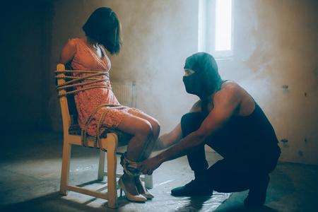 Una foto di una ragazza rapita seduta su una sedia. Archivio Fotografico