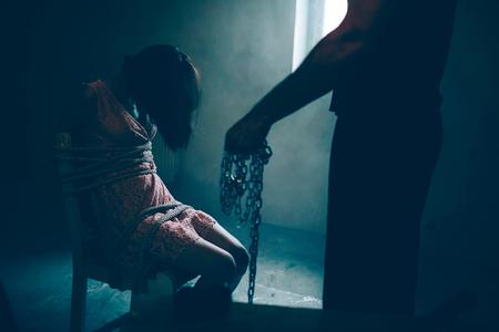Immagine scura del rapitore in piedi accanto alla sua vittima.