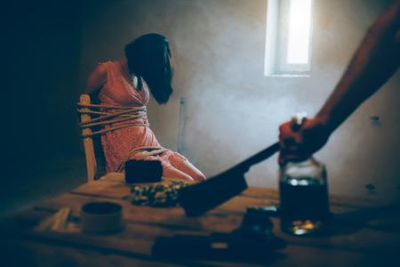 Una foto di una ragazza seduta su una sedia e legata con delle corde. È senza coscienza. La ragazza castana sta sedendosi vicino alla piccola finestra. La stanza è buia. La mano dell'uomo sta tenendo un grosso coltello. È sdraiato sul tavolo.