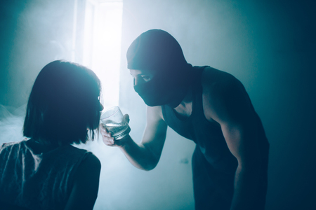 Tied girl is leaning to glass of water that man in mask is holding.