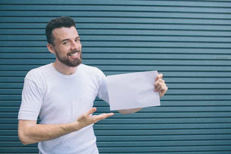 Nice and positive man iss standing and smiling. He is posing and looking at camera. Guy is holding piece of paper and poiting on it with hand. Isolated on striped and blue background.