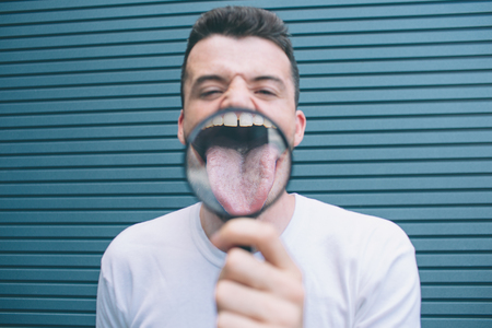 Funny man is standing and showing tongue through lenz. It is zoomed in. Guy is holding thing with one hand. Isolated on striped and blue background. Stock fotó