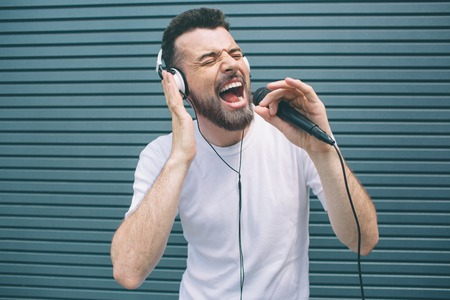 Happy musician is enjoying listening to music. He wears headphones and singing. Guy is using karaoke. Man is singing ot loud. Isolated on striped and blue background.