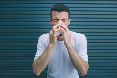 Guy in white shirt is suffering. He is covering nose with white napkin. Man is coughing and sneezing. Isolated on striped and blue background.
