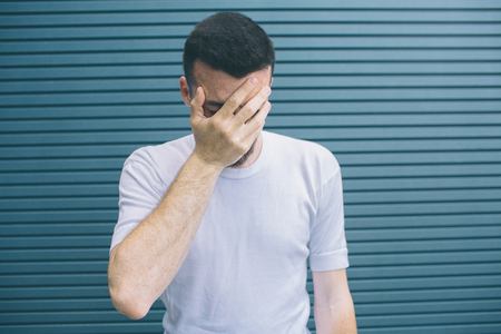 Upset man is standing and covering face with hand. He os unhappy. Guy feels shame. Isolated on striped and blue background.