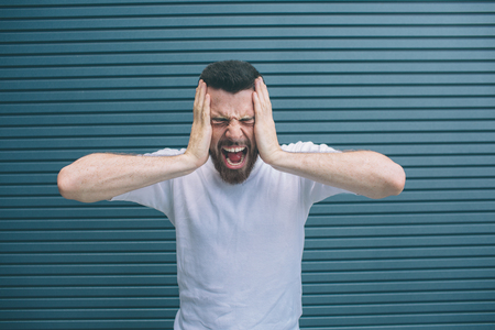 A picture of guy suffering from headache. He is holding hands on face and screaming. He feels terrible. Isolated on striped and blue background.