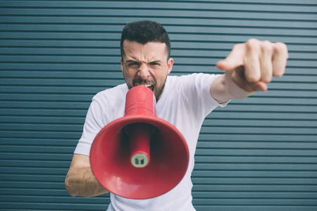 Serious guy is screaming in megaphone. He is holding it with one hand and pointing on camera. Also guy is looking at it. Isolated on striped and blue background. 写真素材