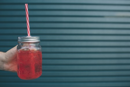 A picture of mans hand holding glass cup of red lemonade. It has straw in it. Isolated on striped and blue background