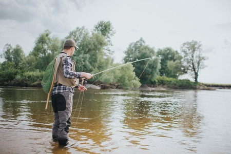 Adult stands in shallow and holding fly rod in hands. He is fishing. Guy is holding fly rod in one hand and part of spoon in the other one. Also man has a fishing net on the back. Archivio Fotografico