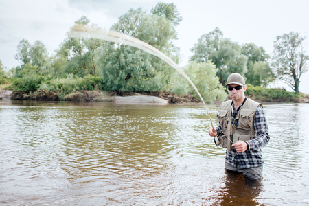 A picture of man holding fly rod. It is vibrating. Guy holds part of spoon in the other hand. He stands in water. He looks serious and cool.
