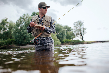 A picture of man holding box with flies and plastic artificial baits. He is holding one of them in hand. Also guy has a fly rod. He is holding it with another hand. Man looks straigght forward. Stock fotó