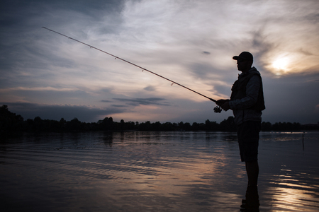 It is evening outside. Fisherman stands in shallow and fishing. He holds fly rod in hands. There is a reel under it. He stands without moving.
