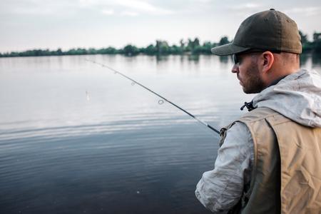 Wytnij widok rybaka stojącego tyłem do aparatu. Patrzy w prawo. Facet ma w rękach wędkę. Na zewnątrz jest chłodno, więc mężczyzna nosi sweter, kamizelkę i czapkę.