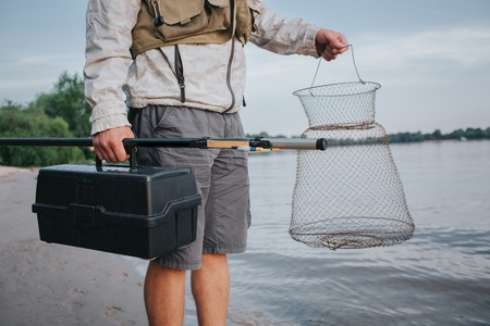 A picture of man holding fishing net and plastic black box in hands. Also he has fly rod in the right one. Guy is standing at the wart shore. Stock Photo
