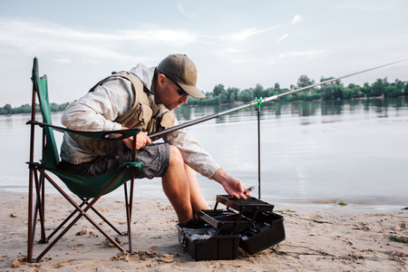 Fisherman is sitting in folding  and leaning forward to opened black plastic box. Guy holds fly rod and plastic bait in hands. It gets chilly outside.