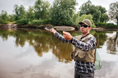 A picture of man stands in water and waving with fly rod. He is going to fish. Guy has fishing net on the back. He looks serious and calm. 写真素材
