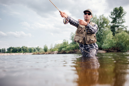 Fisherman in action. Guy is throwing spoon of fly rod in water and holding part of it in hand. He looks straight forward. Man wears special protection clothes.