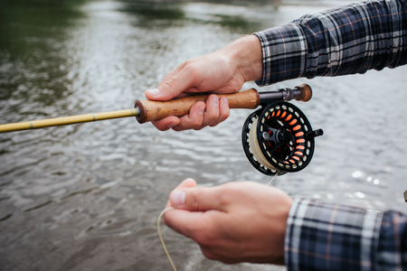 A picture of mans hands holding spinning. There is a non-inertial reel under fly rod. Guy is holding part of spoon in hand. Фото со стока - 105920423
