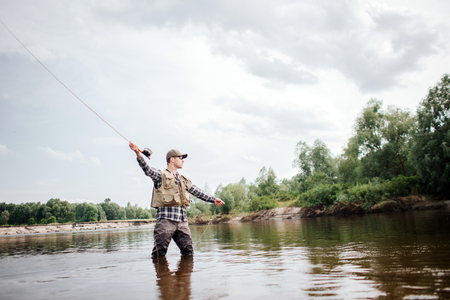 A picture of man holding up fly rod in right hand. He is standing in shallow water and looking straight. He is ready to throw part of spoon with baits in it to catch fish. Archivio Fotografico