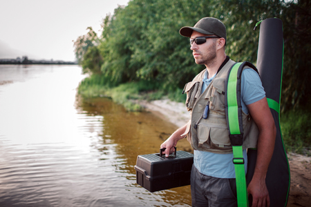 Serious fisherman is standing in shallow and looking straight forward. He holds plastic black box in one hand and cover for fli rod with another one.