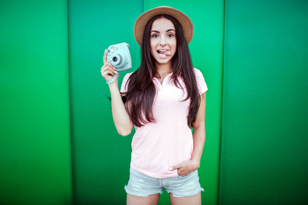 Funny and poitive girl stands and shows her tongue. Girl holds blue camera in one hand and keeping other one in pocket. Isolated on green and striped background. Stock Photo