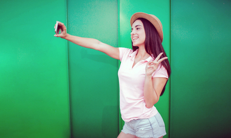 Pretty girl stands and poses. She holds phone in hand and makes selfie. Girl has a piece symbol. She made it with her fingers. Isolated on striped and green background.