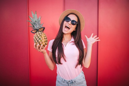 Happy and excited brunette stands and holds pineapple in one hand. It has sunglasses. Girl wears it as well. She is amazed. Isolated on red and striped background.